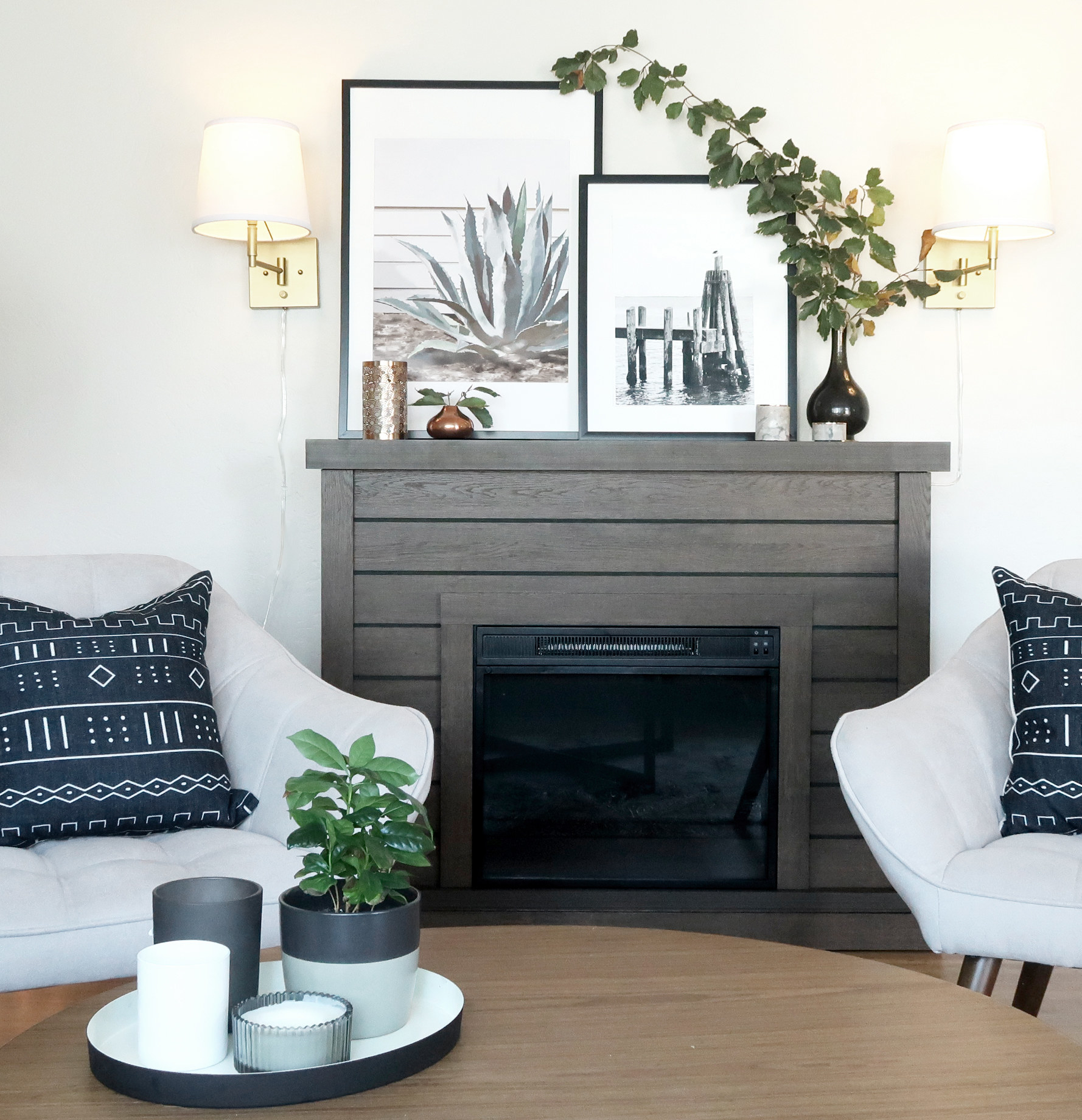 A faux fireplace, with decor on its mantle, is the focal point between two armchairs