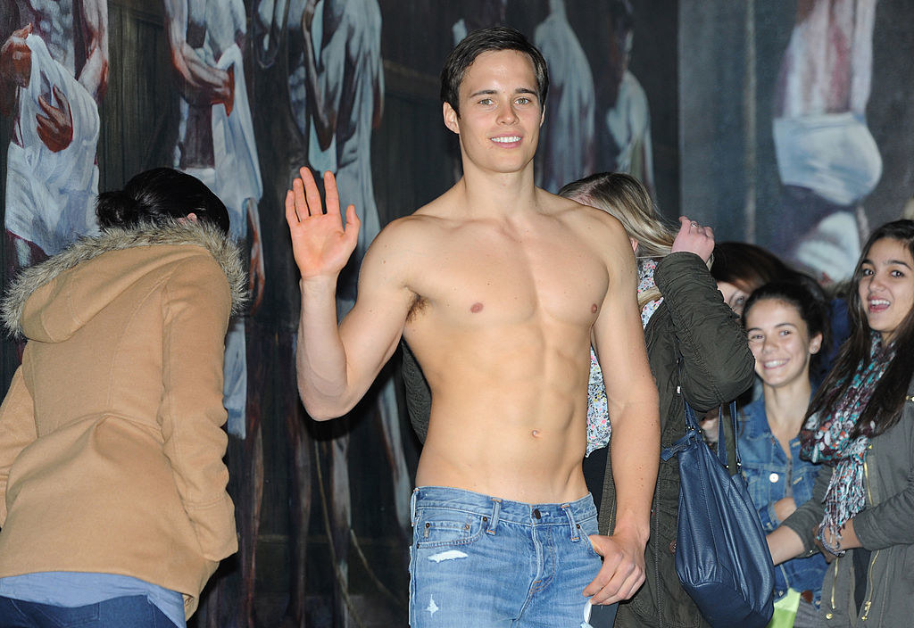 A shirtless guy waving at the camera while standing in front of an Abercrombie & Fitch.