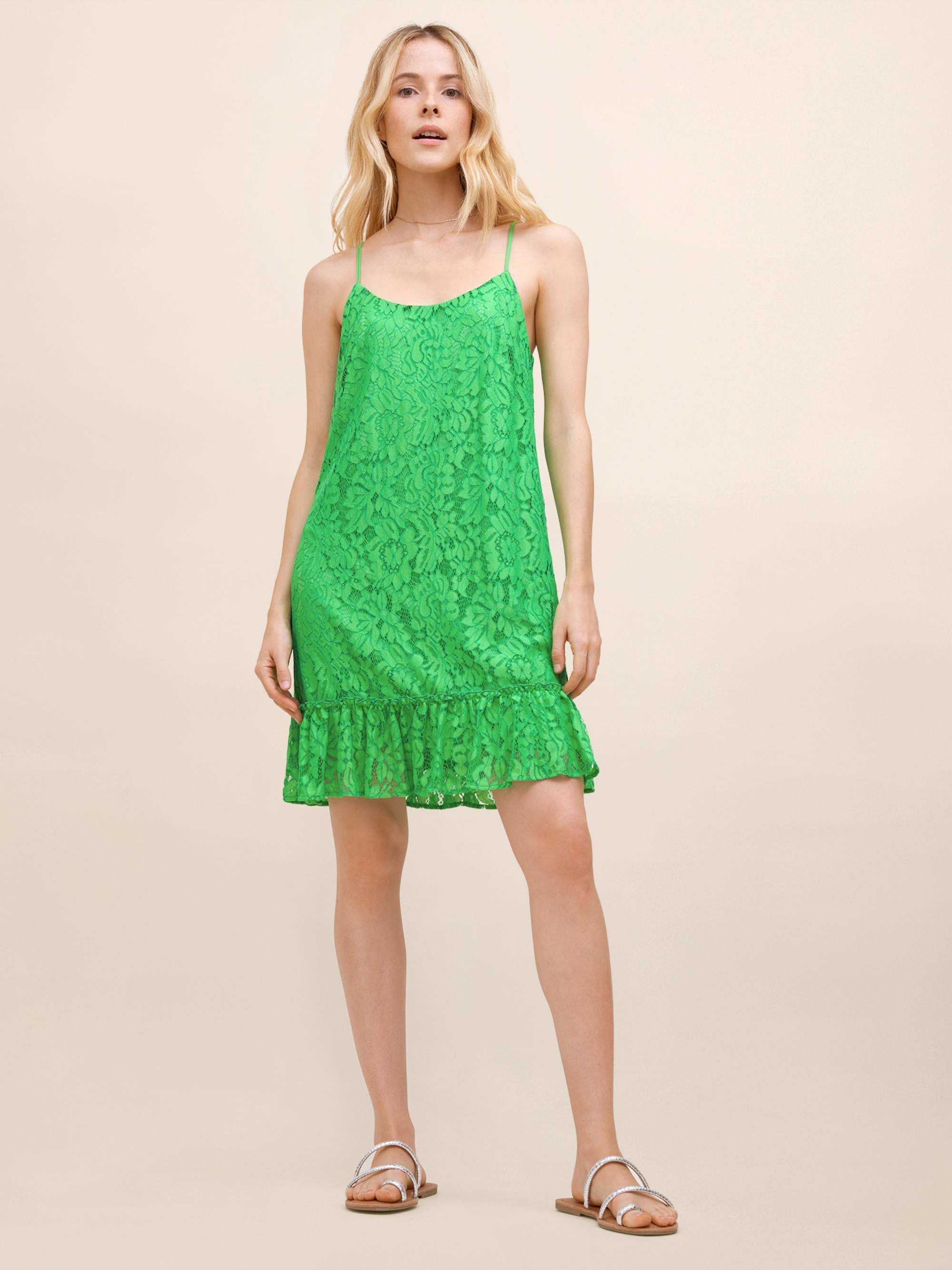 model in a green lace sleeveless dress with ruffle hem