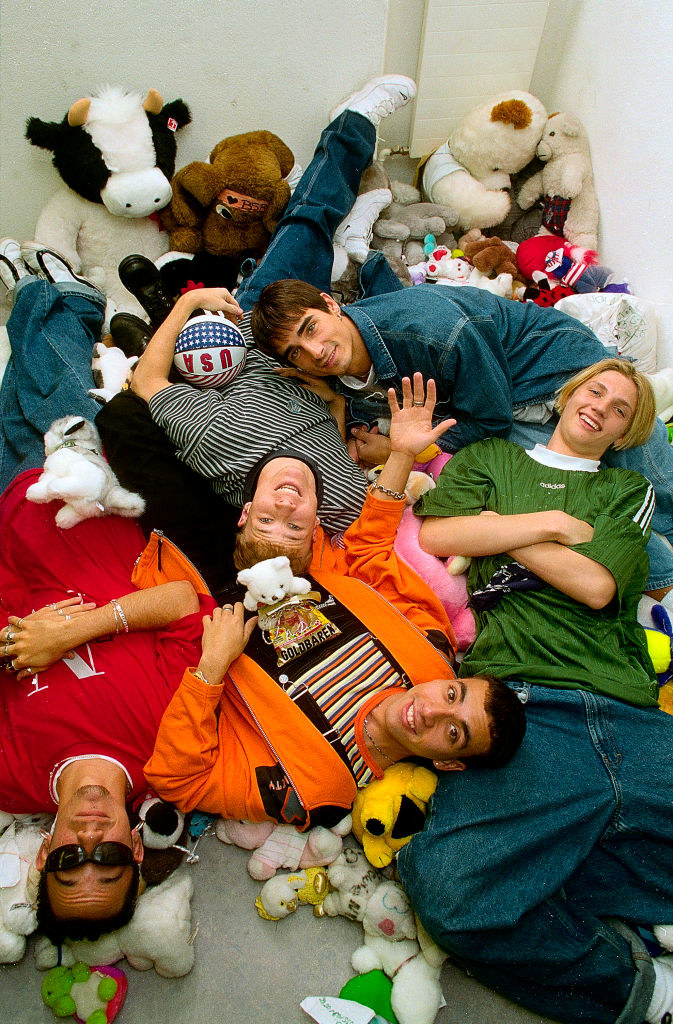 A photo of the Backstreet Boys lying on a bunch of stuffed animals.