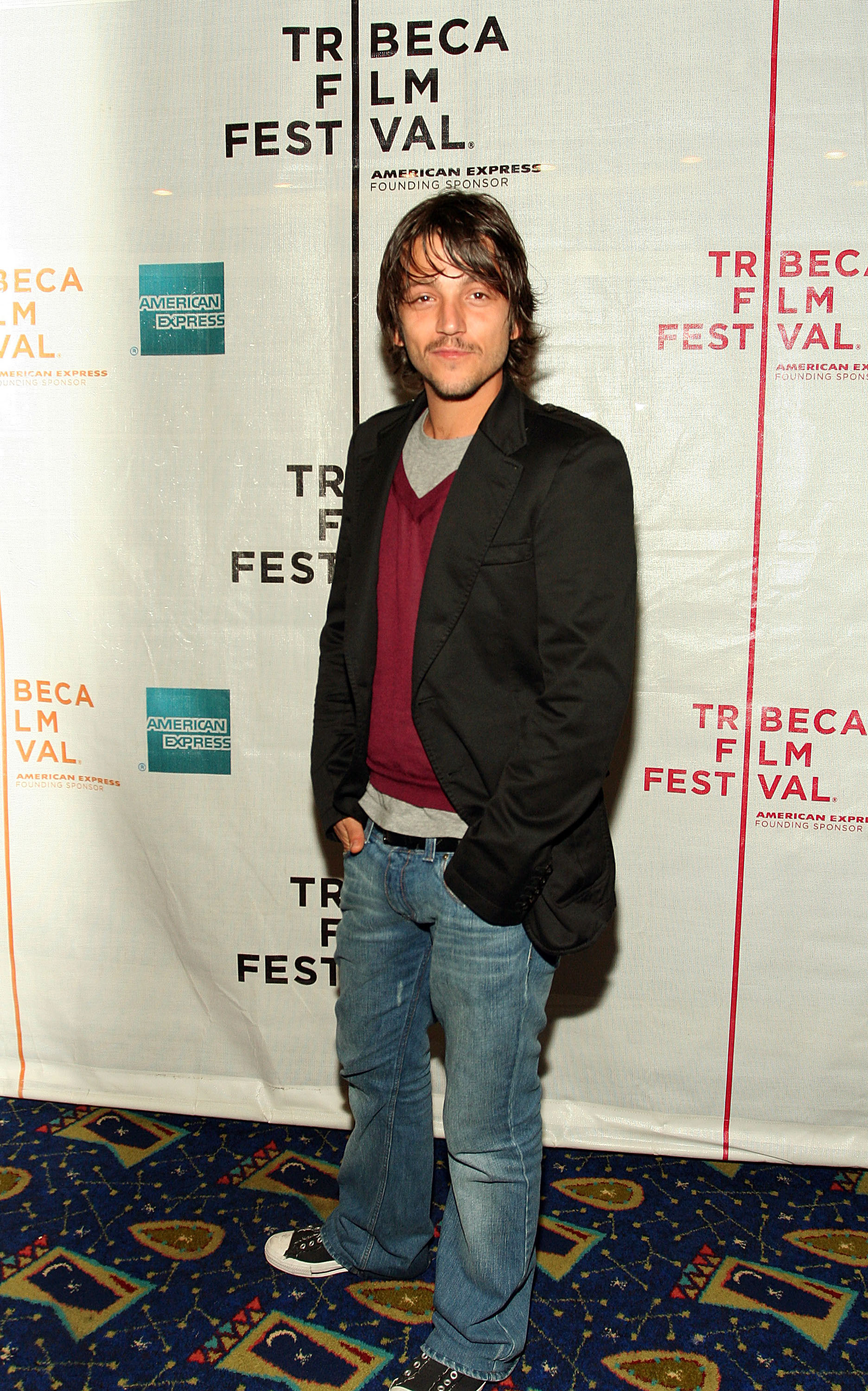 Diego Luna wearing bootcut jeans and black Converses.