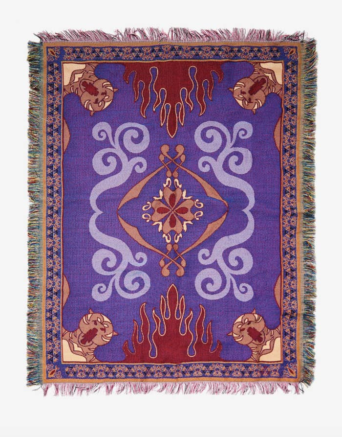 a woven throw featuring a purple design with red flames, tigers, and fringed edges