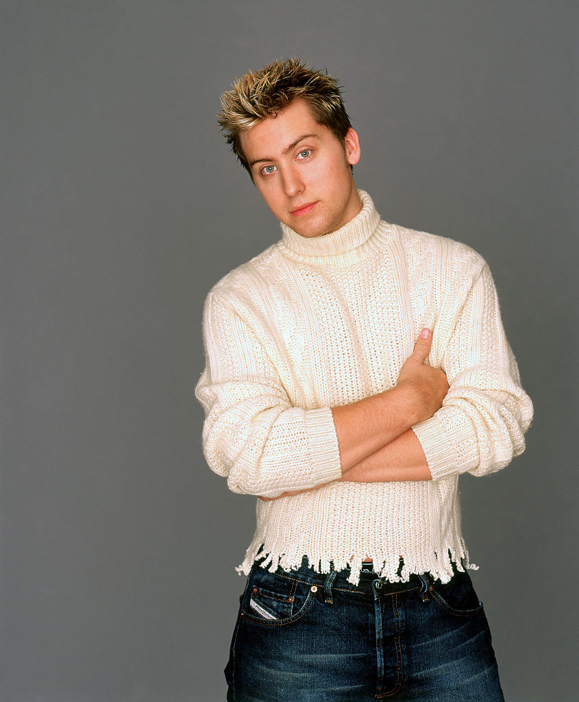 Lance Bass wearing an ivory knitted turtle neck sweater with a the entire bottom portion ripped.