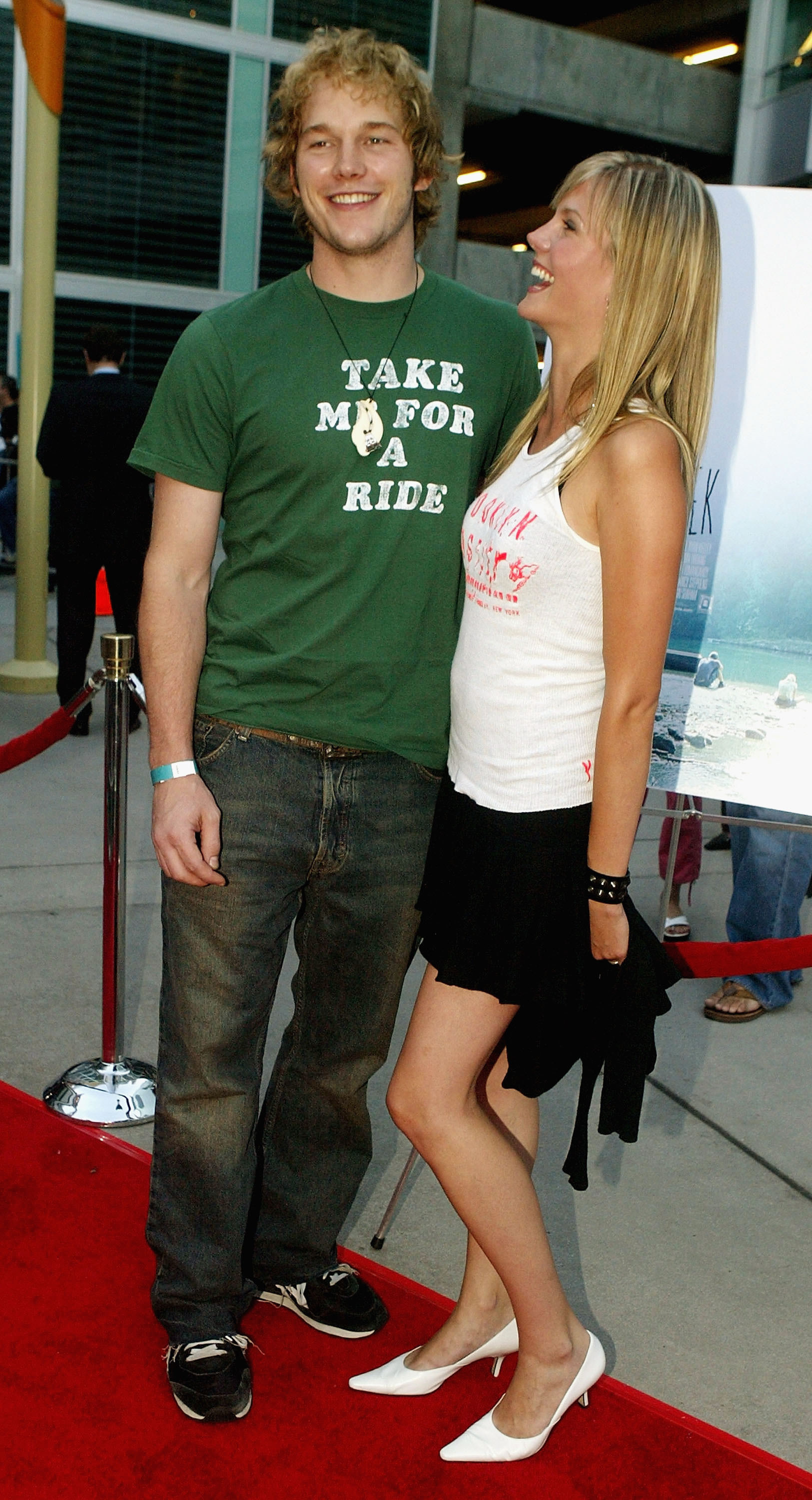 """A photo of Chris Pratt wearing a green T-shirt with """"Take Me For A Ride"""" written on it."""