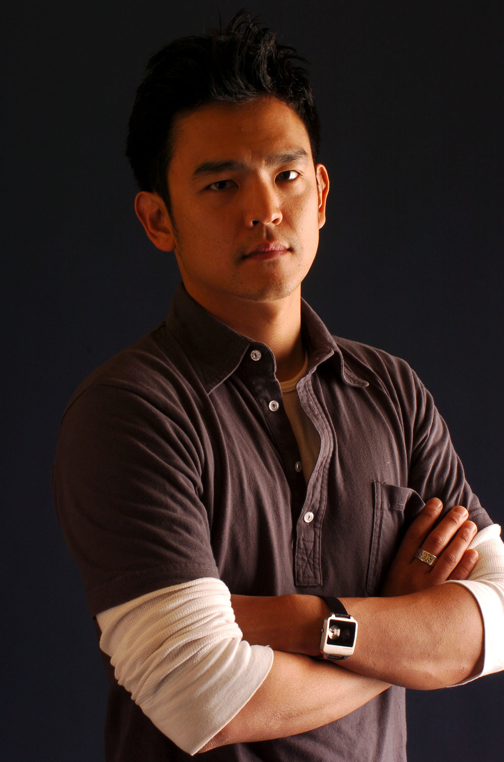 A photo of John Cho wearing a white thermal underneath a dark gray polo.
