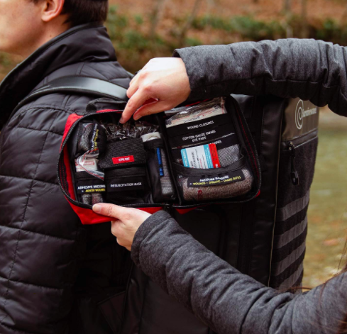 Hikers access red mini first aid kit from one of their backpacks