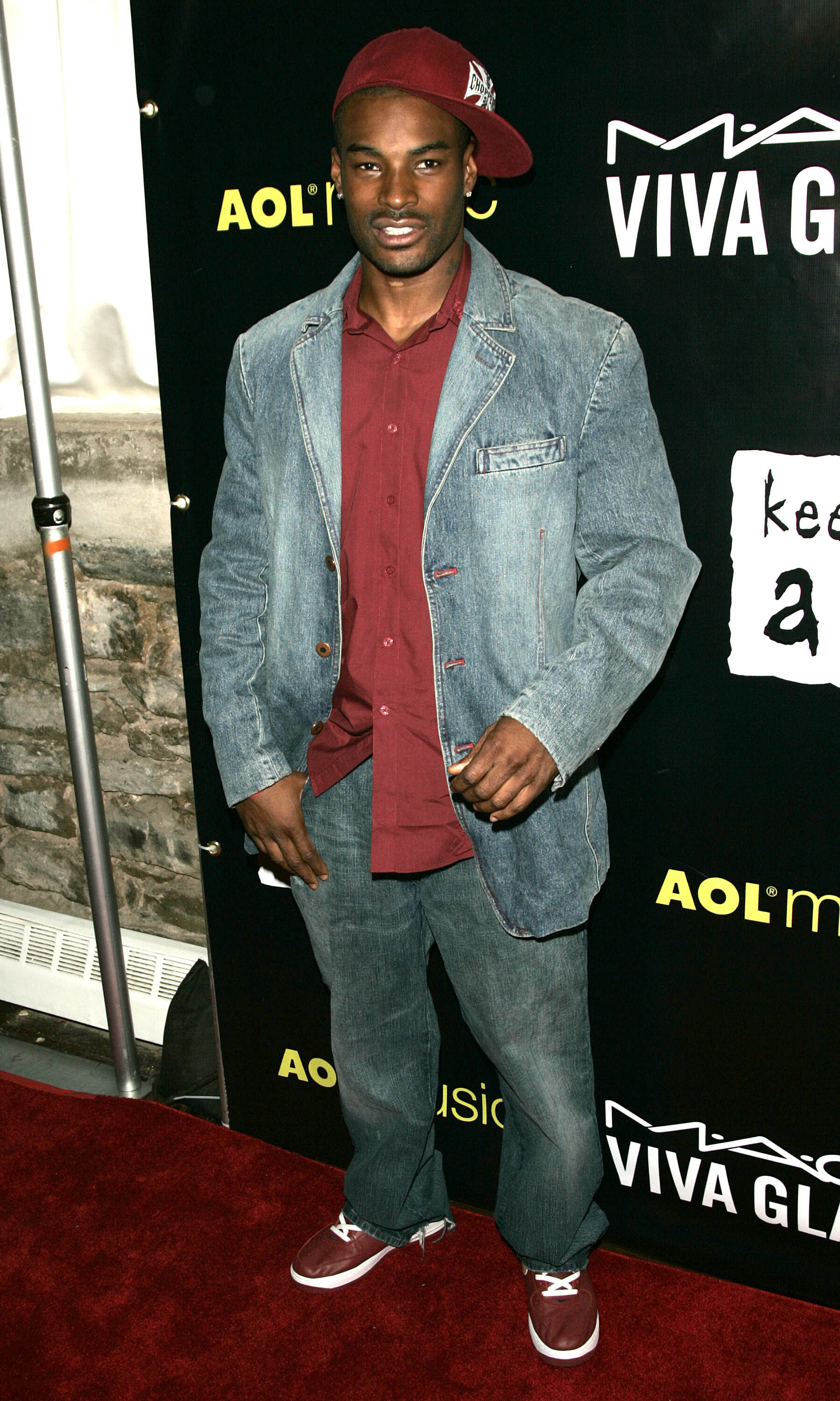 A photo of Tyson Beckford on a red carpet wearing a large denim blazer with jeans.