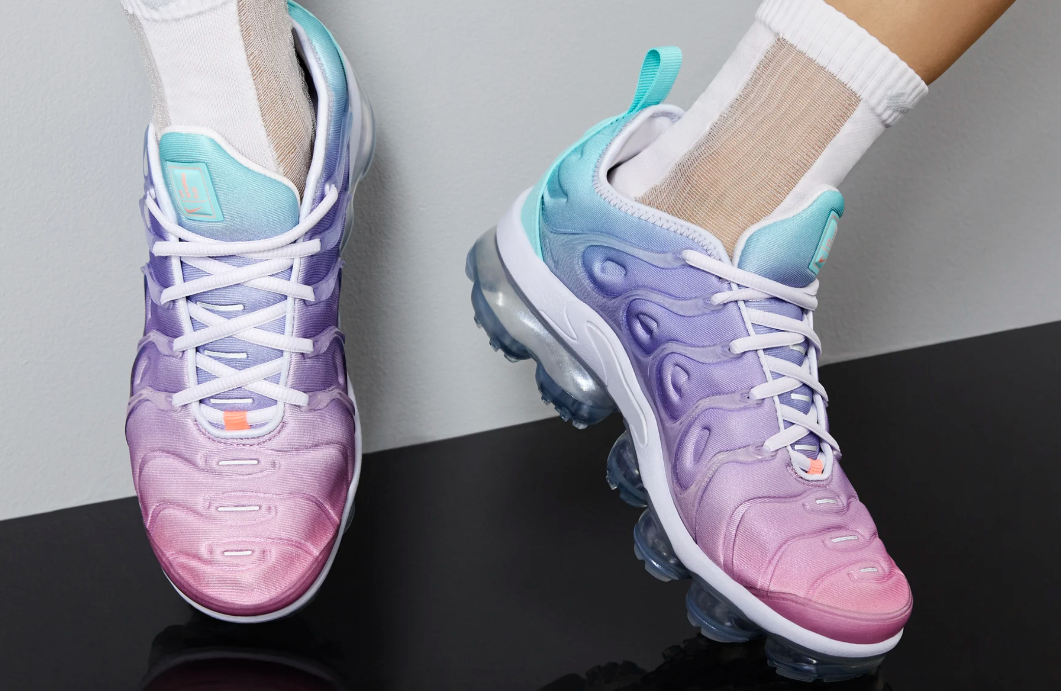 The shoes on feet in a pink, purple, blue ombre