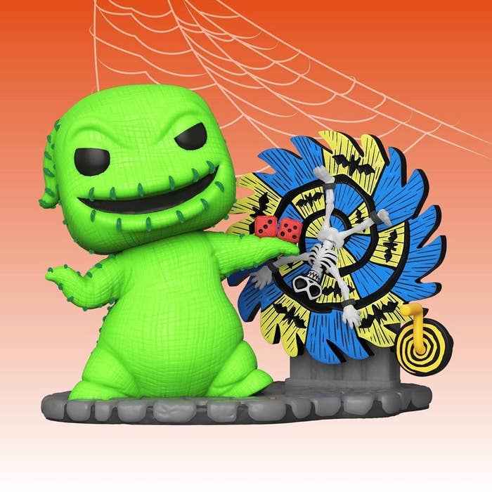 a green oogie boogie figure standing next to a spinning blue and white wheel with dice in hand and a skeleton in the middle