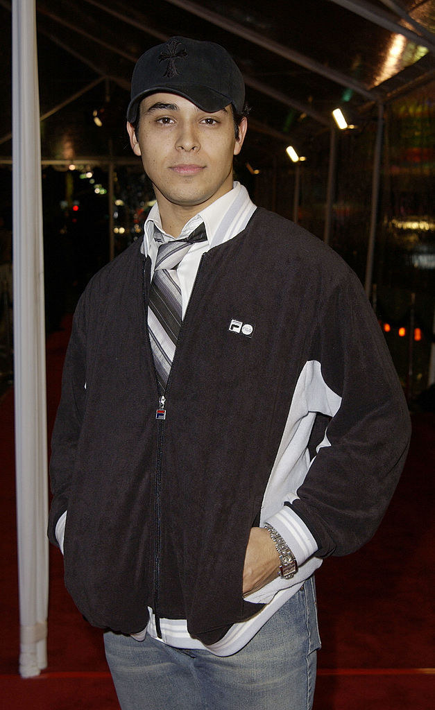 A photo of Wilmer Valderrama wearing a large striped tie worn with a jeans, an untucked button down, and velour jacket.