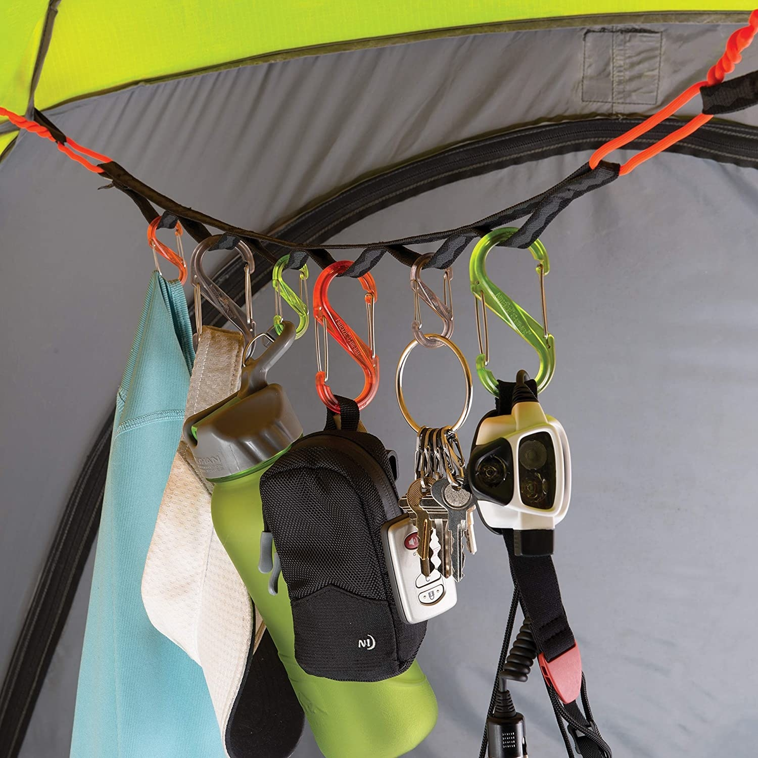strap with fabric rings attached to tent ceiling with twist ties hanging S-Biners and carabiners  hlding gear like water bottles, hats, and keys