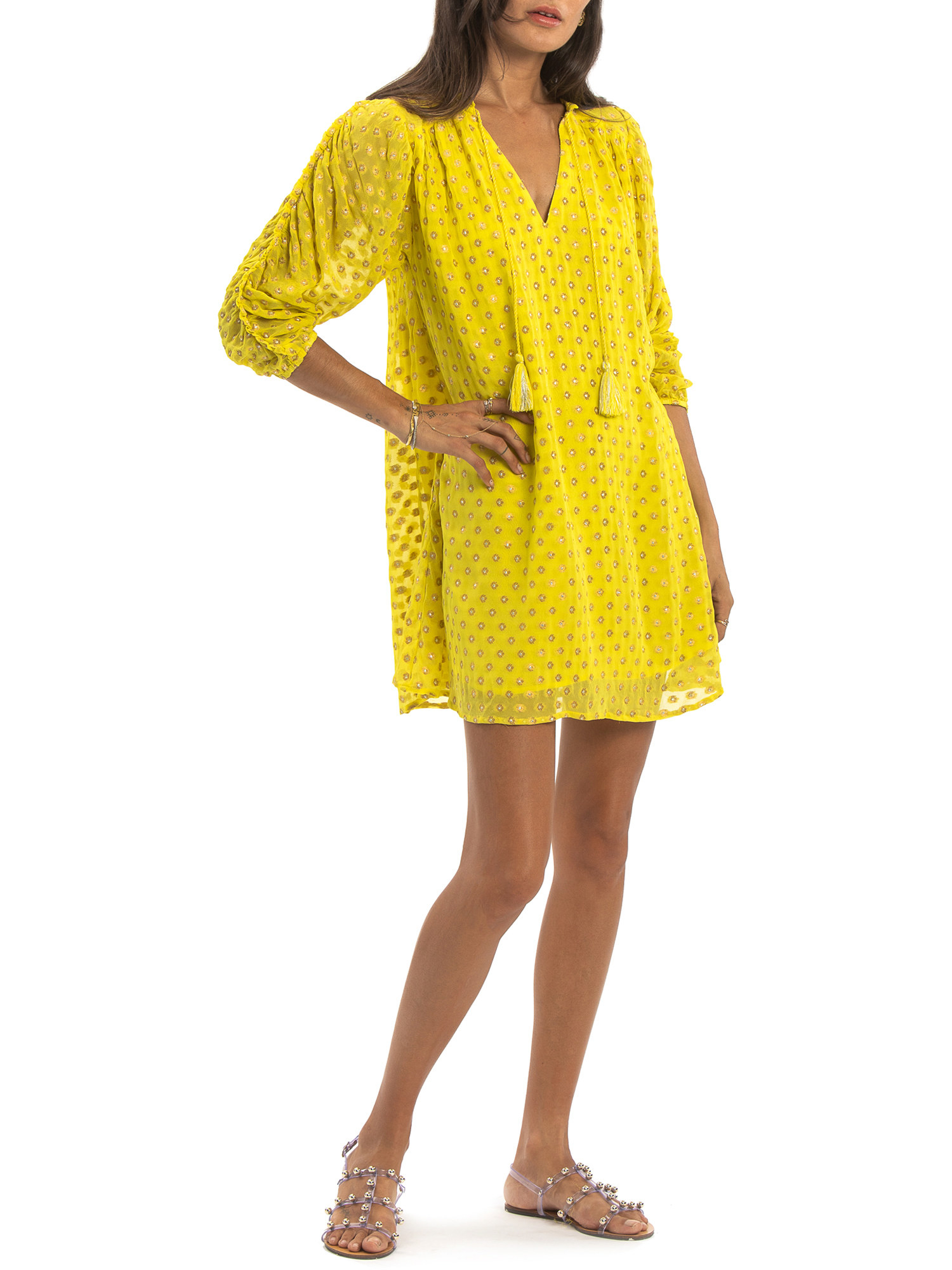 model in a yellow dress with 3/4 sleeves and tassels at the collar
