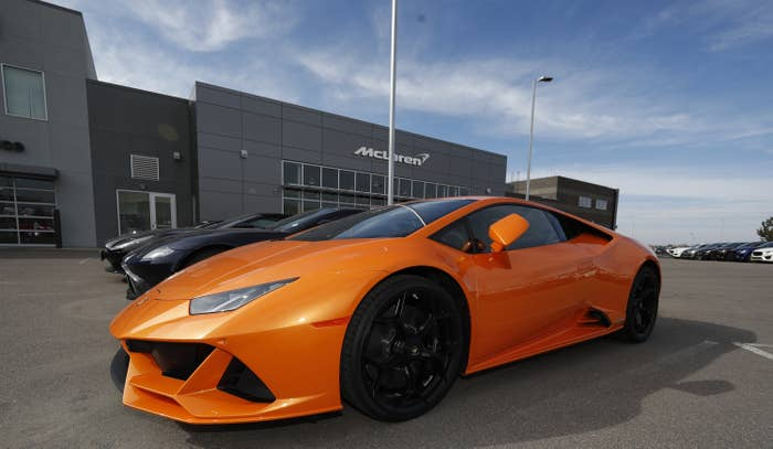 An orange sports car is parked at a dealership