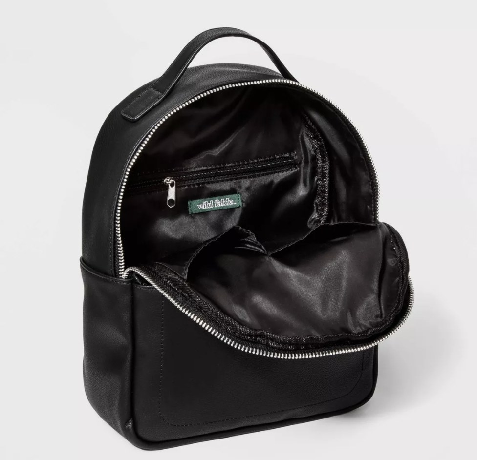 A small black backpack unzippered revealing the interior