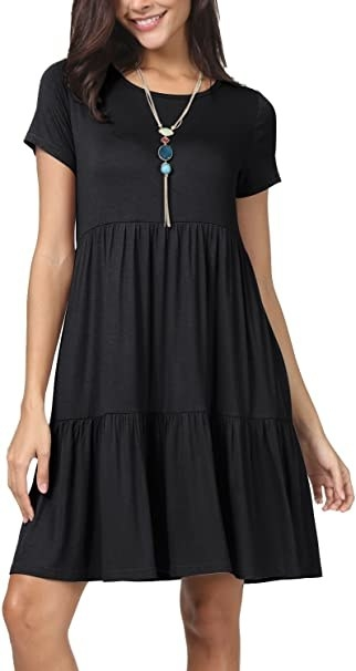 model wearing black short sleeve dress with a ruffle tier along the hem