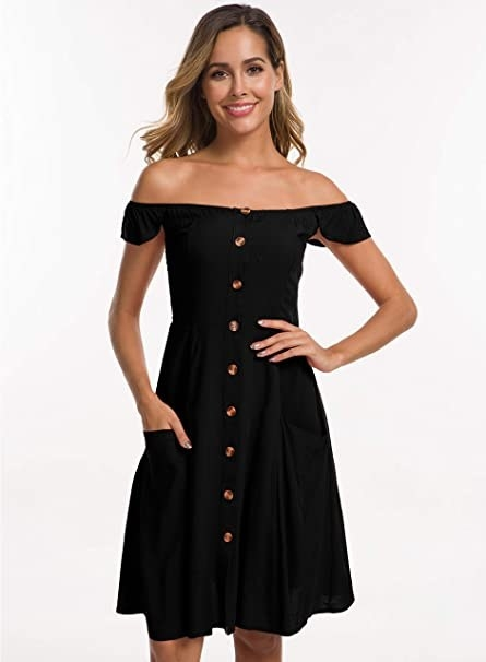 model wearing knee length black dress with buttons down the front and pockets on front with small cap sleeves