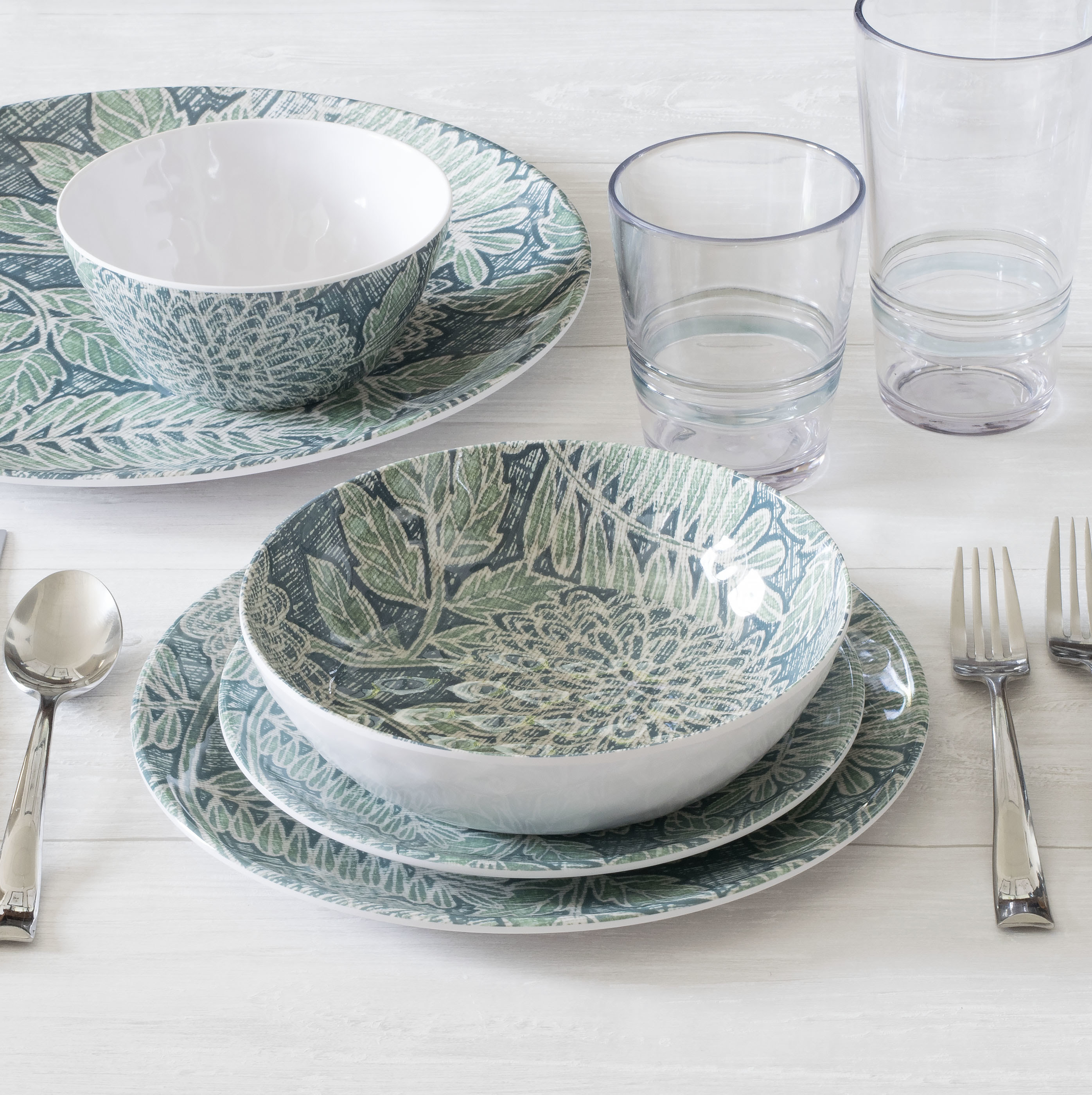 the melamine dishes and bowls with a green and blue leafy pattern inside