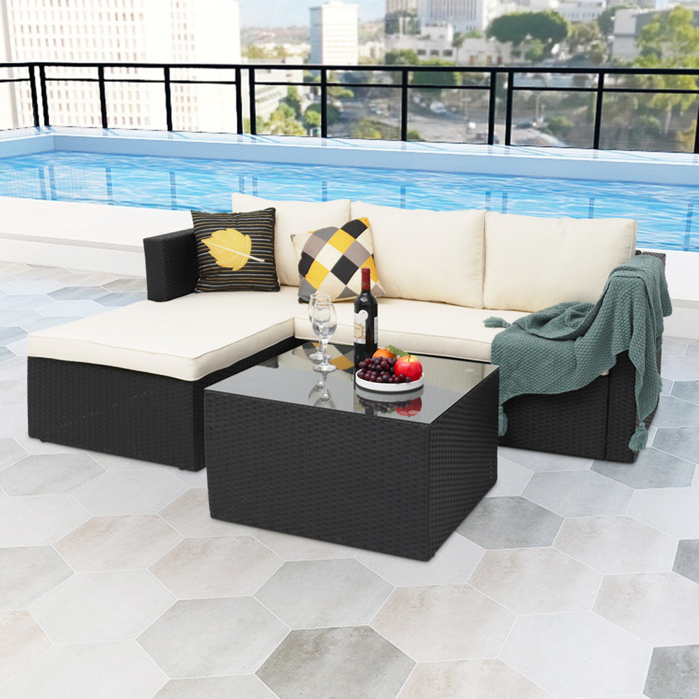 a white outdoor sectional couch with a black woven coffee table