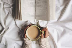 A mug of coffee and an open book against a white blanket