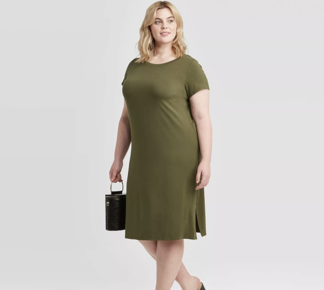 Model wearing an olive green t-shirt dress that hits below the knee