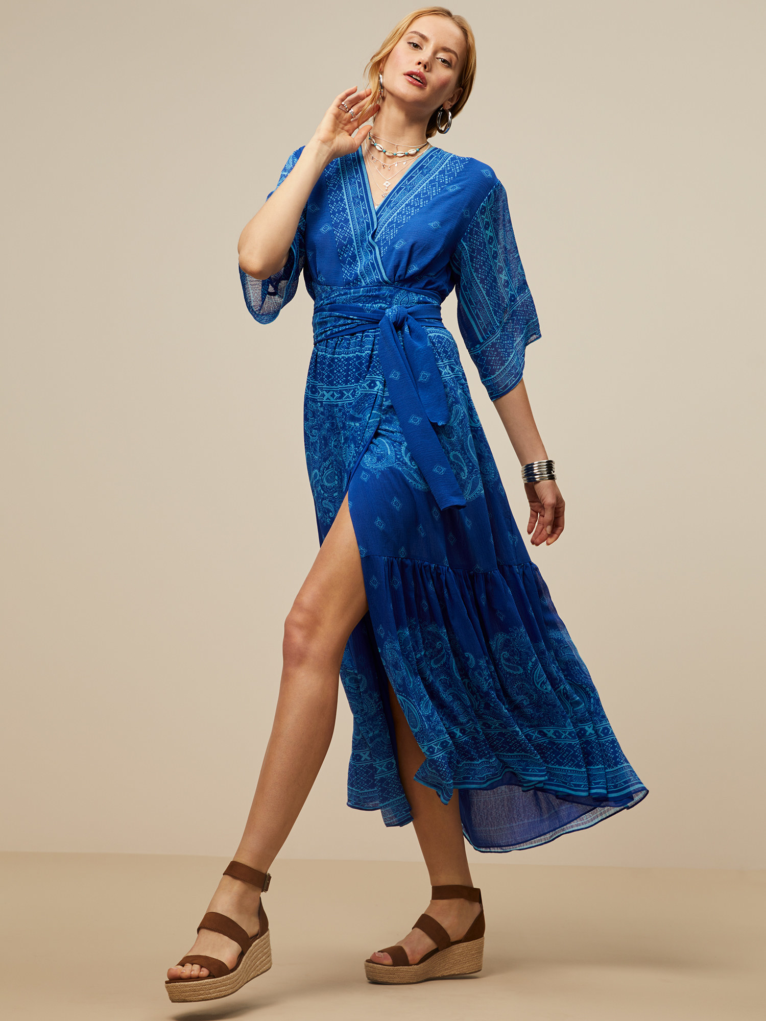 model in a maxi wrap dress in blue paisley with a slit skirt and 3/4 sleeves