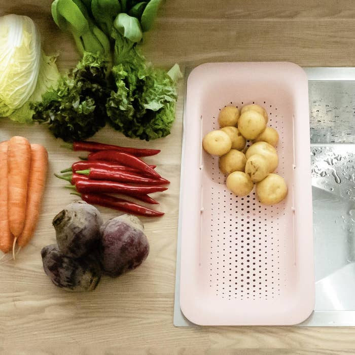 The strainer in pink expanded  to fit in a sink with potatoes in it and other vegetables next to it