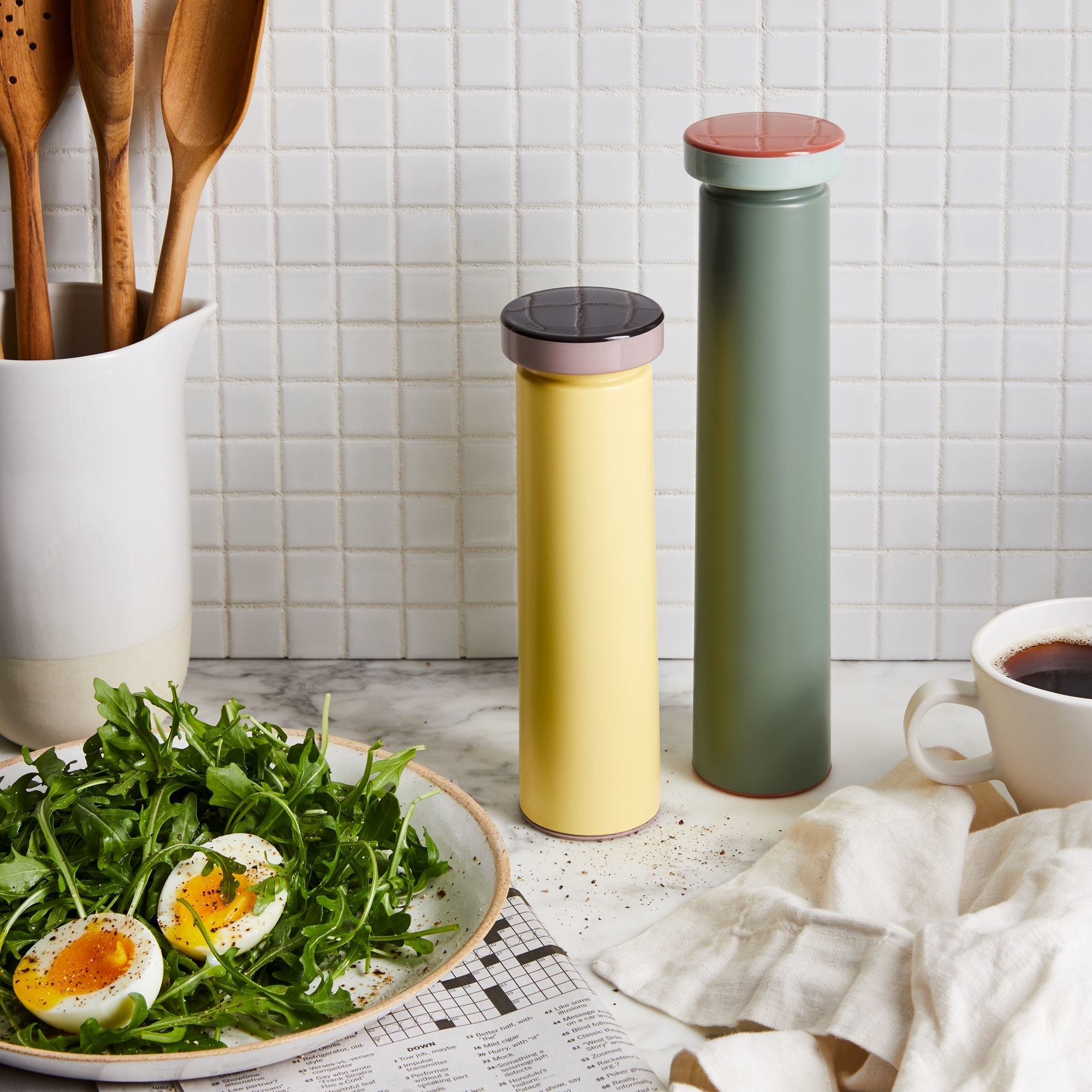 Small yellow and taller green spice grinders sitting on a kitchen counter
