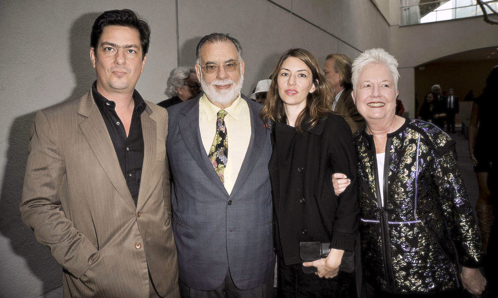 A getty image showing the Coppola family in a line arm in arm, including Roman, Francis, Sofia and Eleanor, their mother