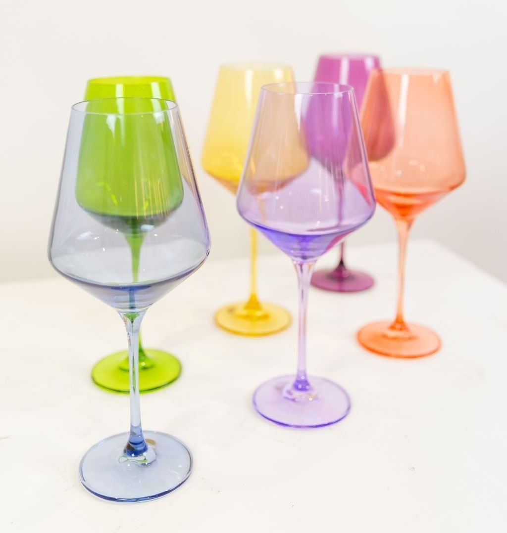 Six wine glasses; one in blue, purple, orange, green, yellow, and pink