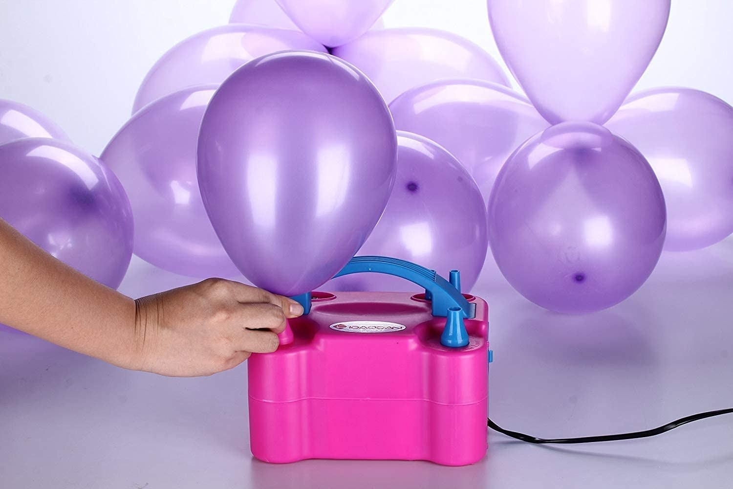 A person using the machine to blow up a metallic balloon