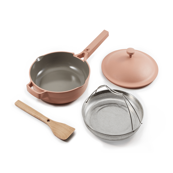 Closeup of the pot and lid in pink, steamer basket, and spatula that's all included
