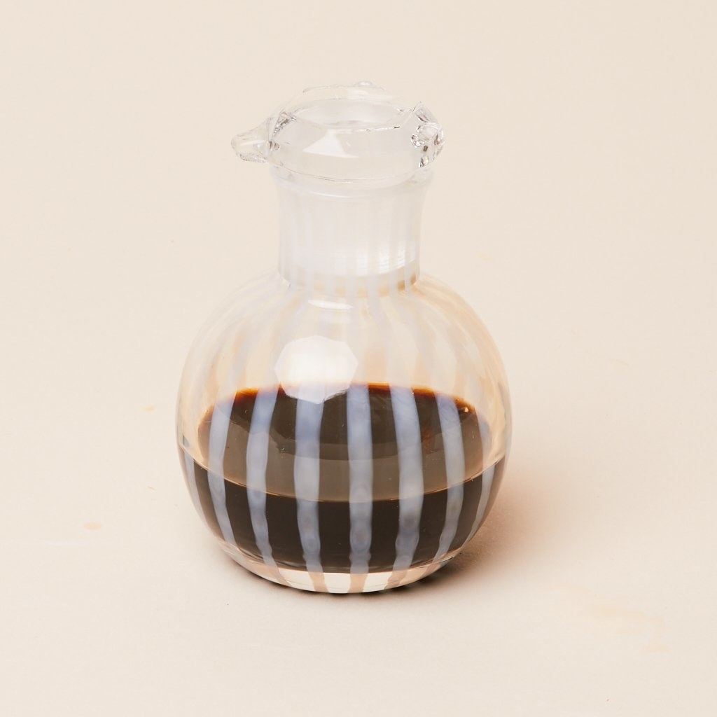 Circular cruet with a spout in clear glass with milky white vertical stripes
