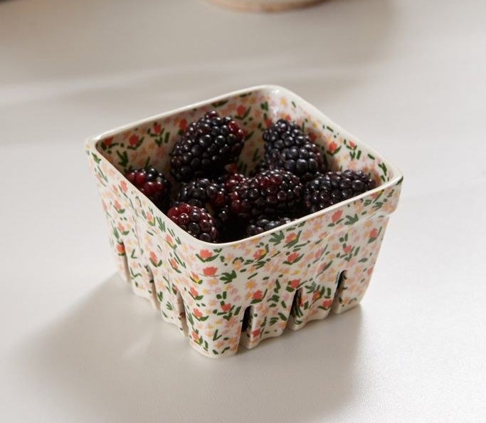 The dish that looks like a berry container in white with small flowers drawn all over it