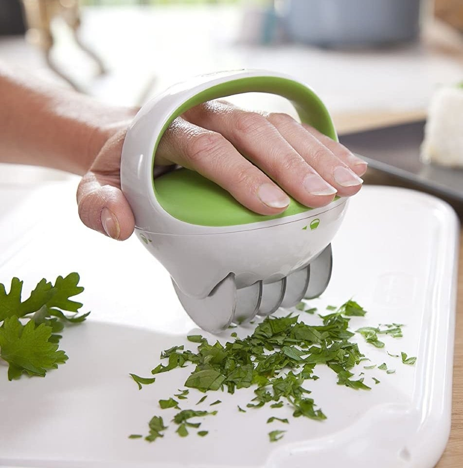 A person mincing herbs with the herb chopper
