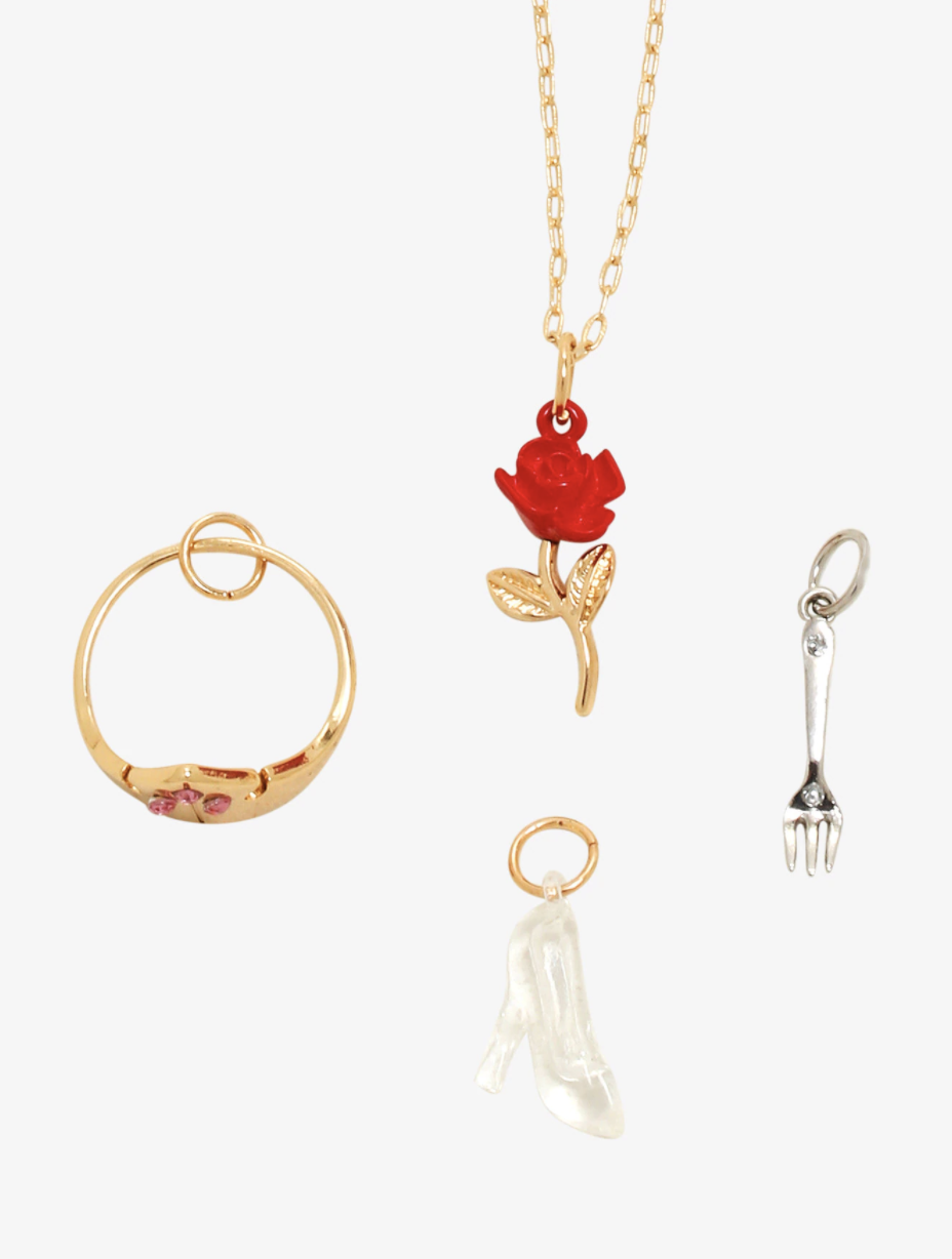 a gold necklace with a single rose charm hanging from it in addition to three other princess-themed charms