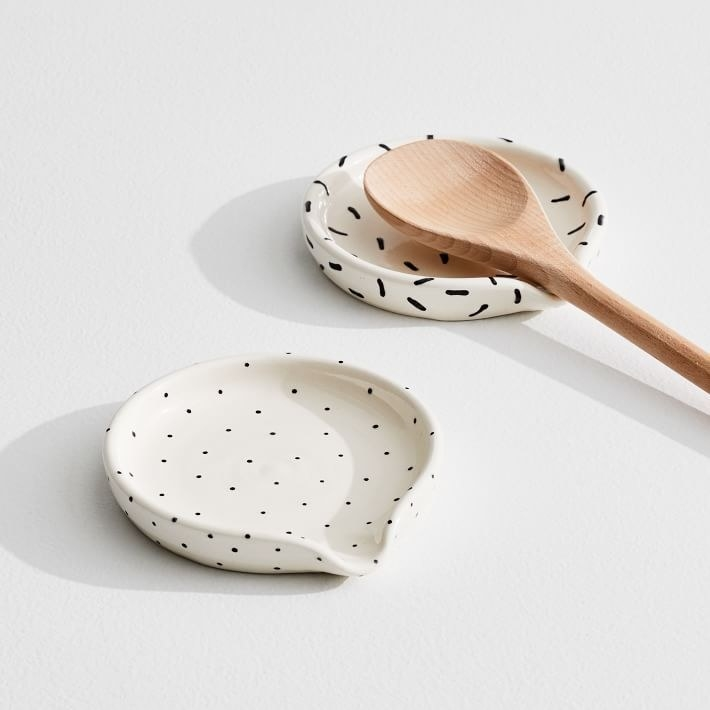 Two spoons rest both white — one with small black dots and the other with long thin lines (like sprinkles) with a wooden spoon on it