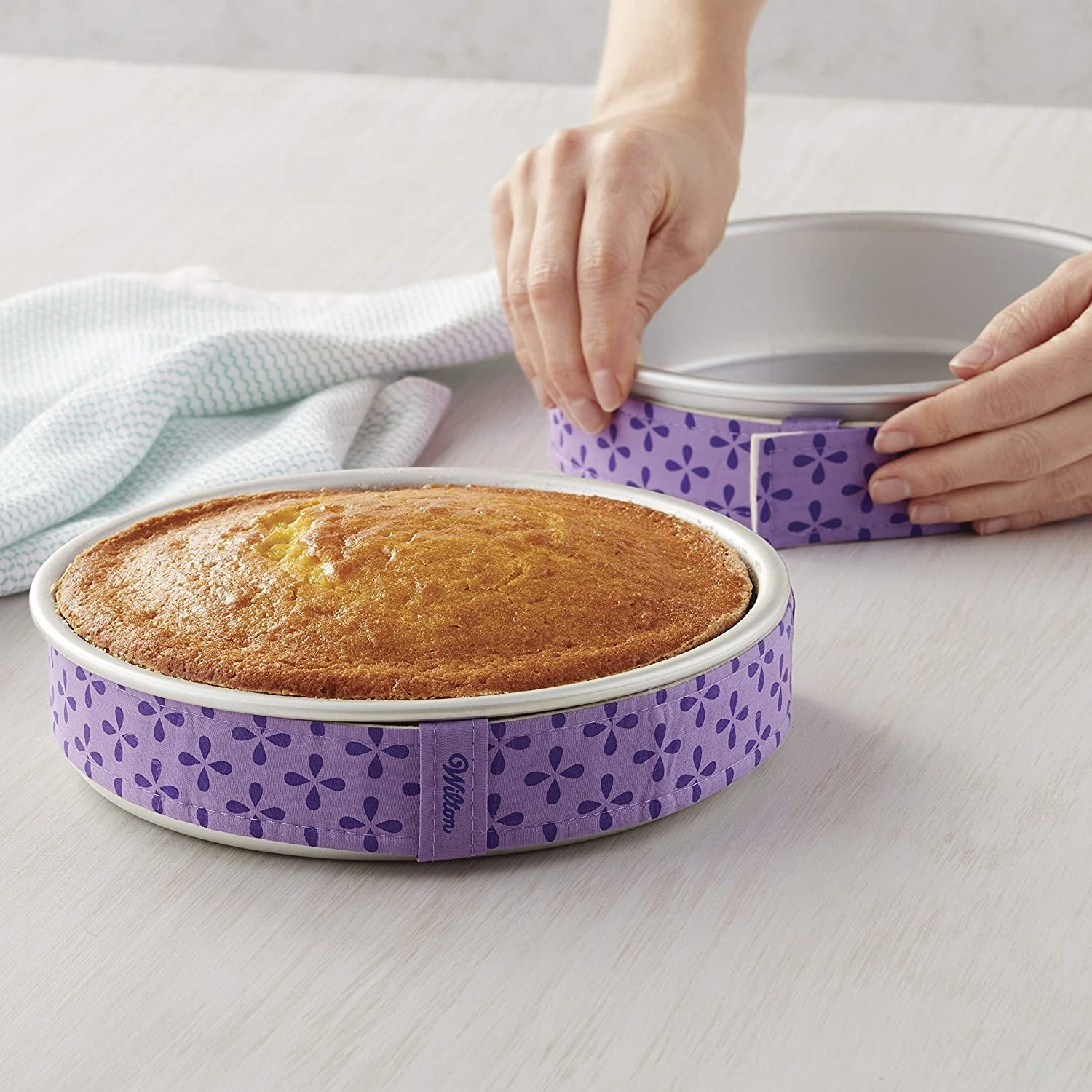 A person attaches the cake strips to a baking pan while another perfectly cooked cake rests next to it