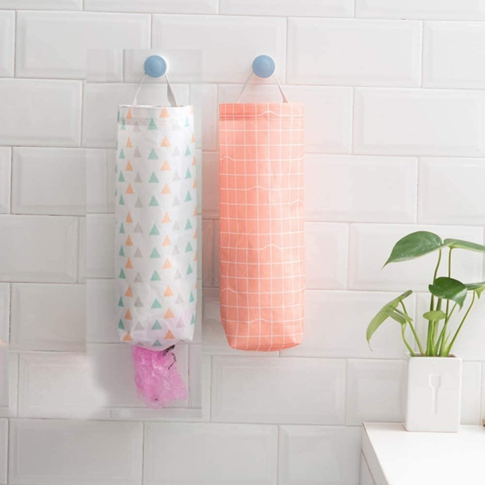 Two  plastic bag holders hanging from a hook on the wall — one is white with green, orange, and grey triangles and the other is onange with white checked pattern
