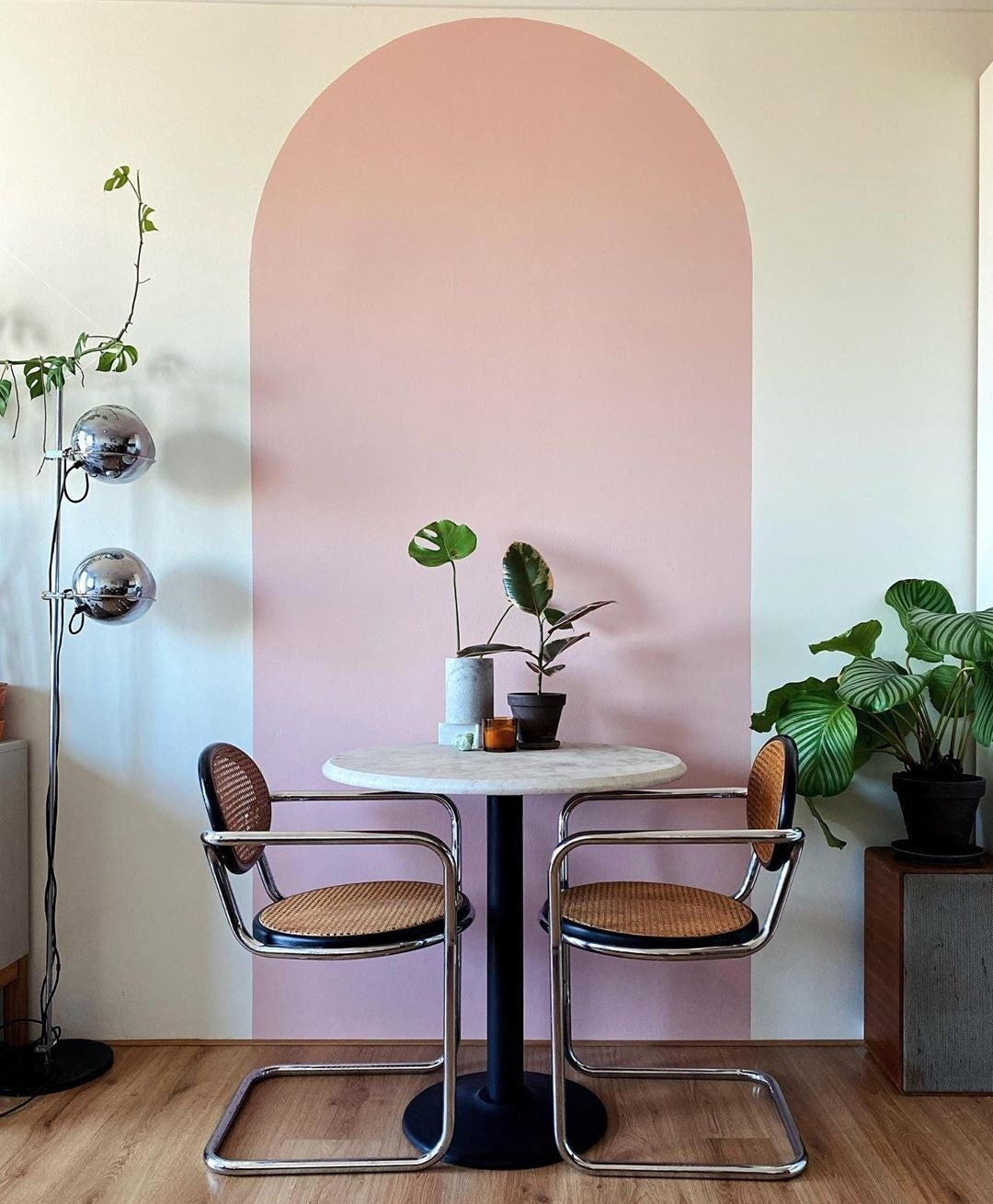 A pink archway is painted on a white wall behind a table and two chairs