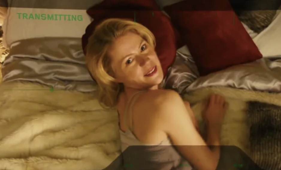 A woman laying on a bed, looking behind her sexually.