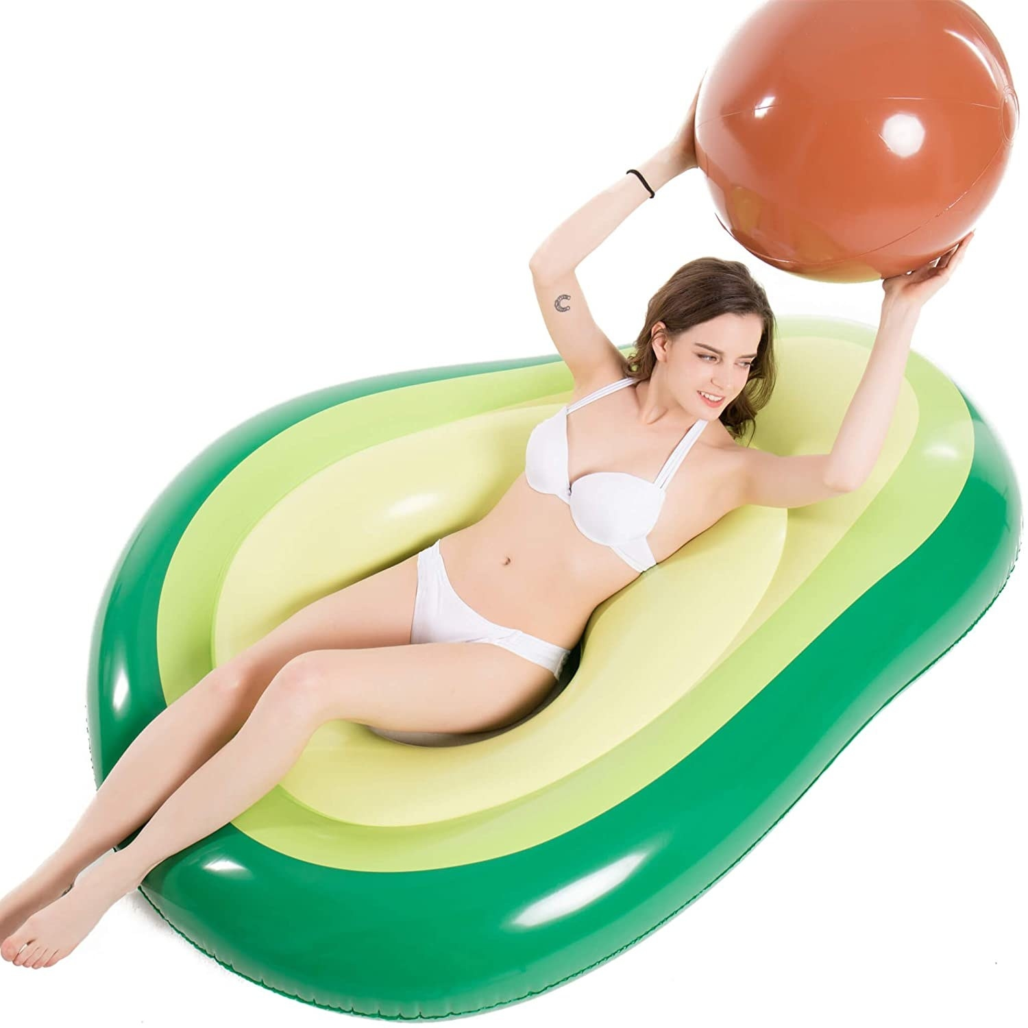 A model sitting in the avocado-shaped float that has a hole in the middle, holding the brown ball