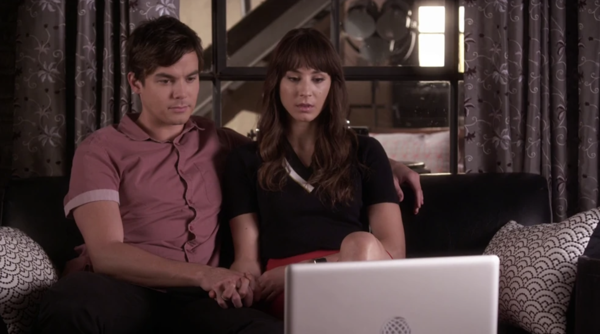 Caleb and Spencer sitting on a couch, holding hands, and looking at a laptop