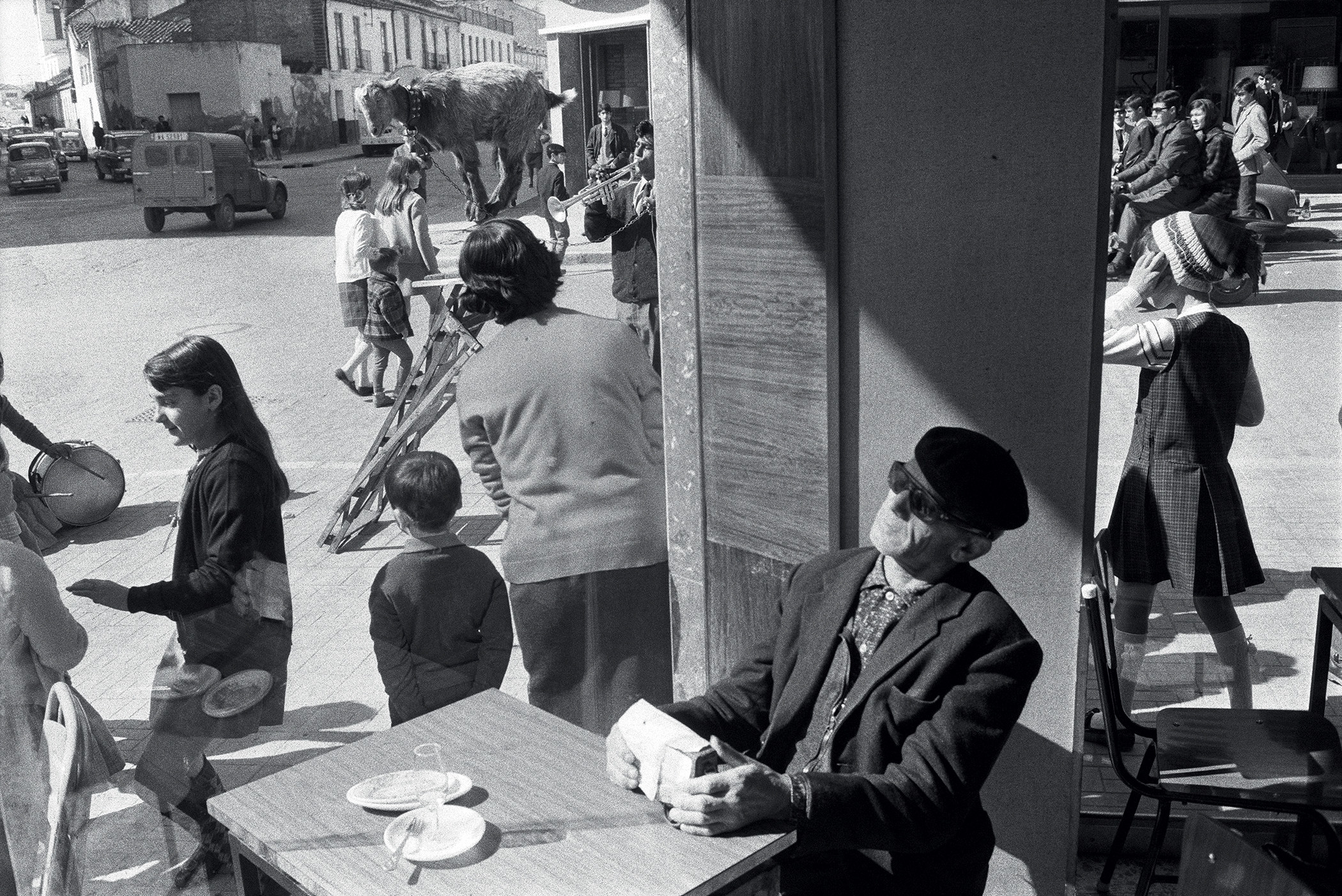 A man in sunglasses sits in a café while crowds of pedestrians are visible through the window