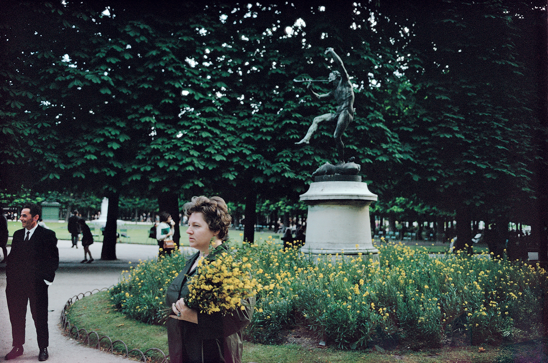 A woman carries flowers through a city park