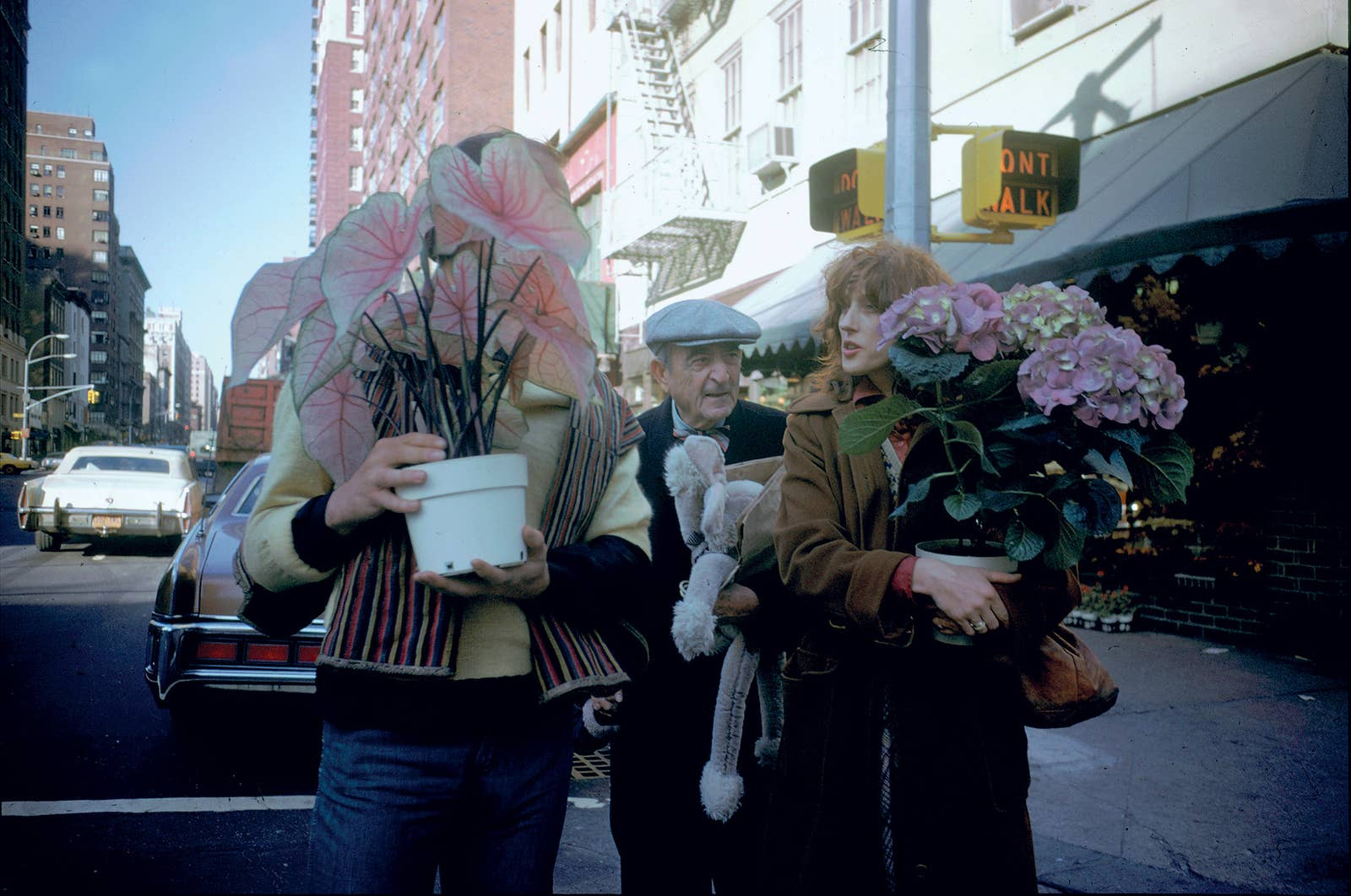 A man and a woman carry flowers on a city street