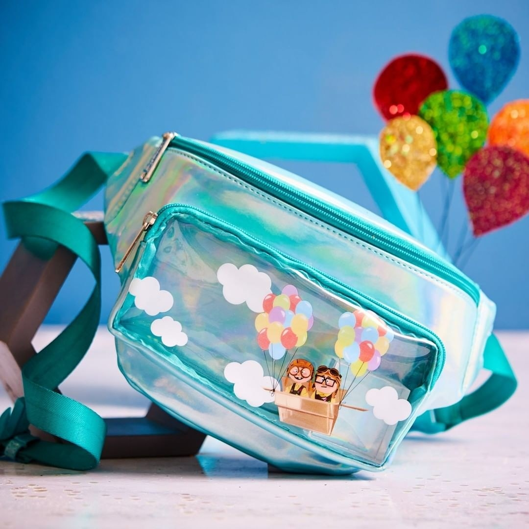 "a light blue iridescent fanny pack with a clear front pocket featuring a young carl and ellie fom ""up"" in a balloon basket"