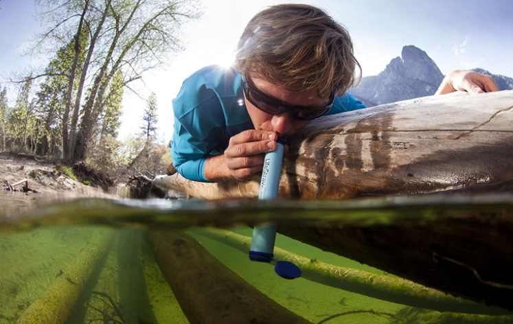 Hiker uses blue personal water filter to drink water from a lake