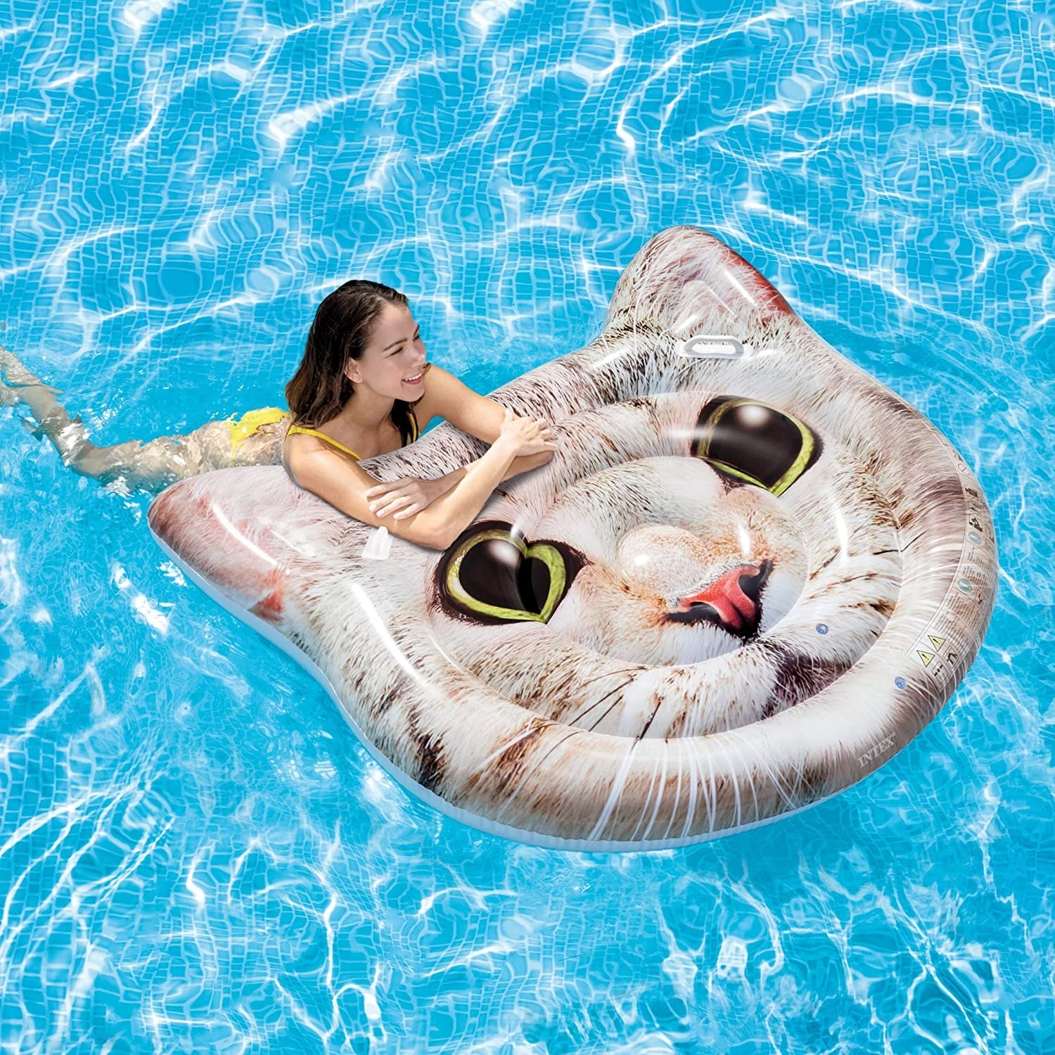 A model in a pool with the float, which is shaped like a cat's head an features a photo of a green-eyed tabby's face