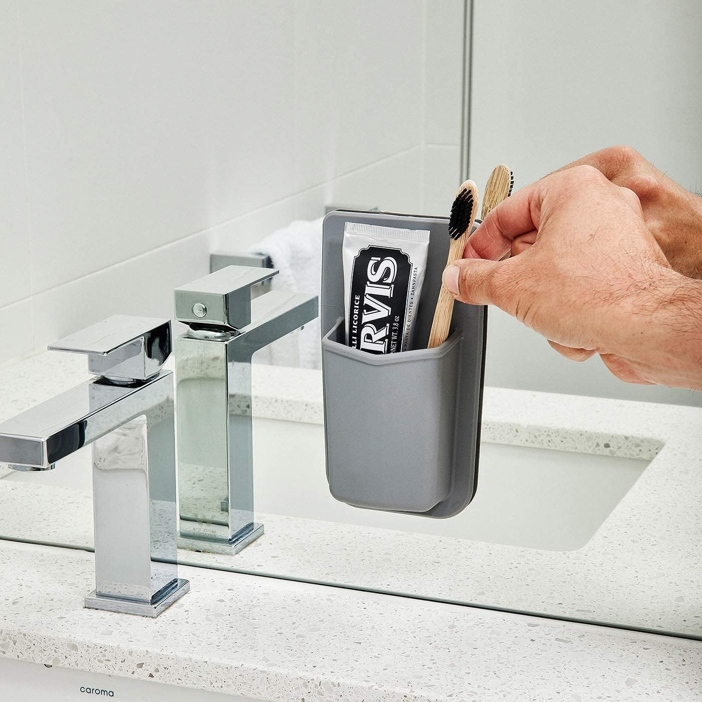 gray silicone toothbrush holder stuck on bathroom mirror