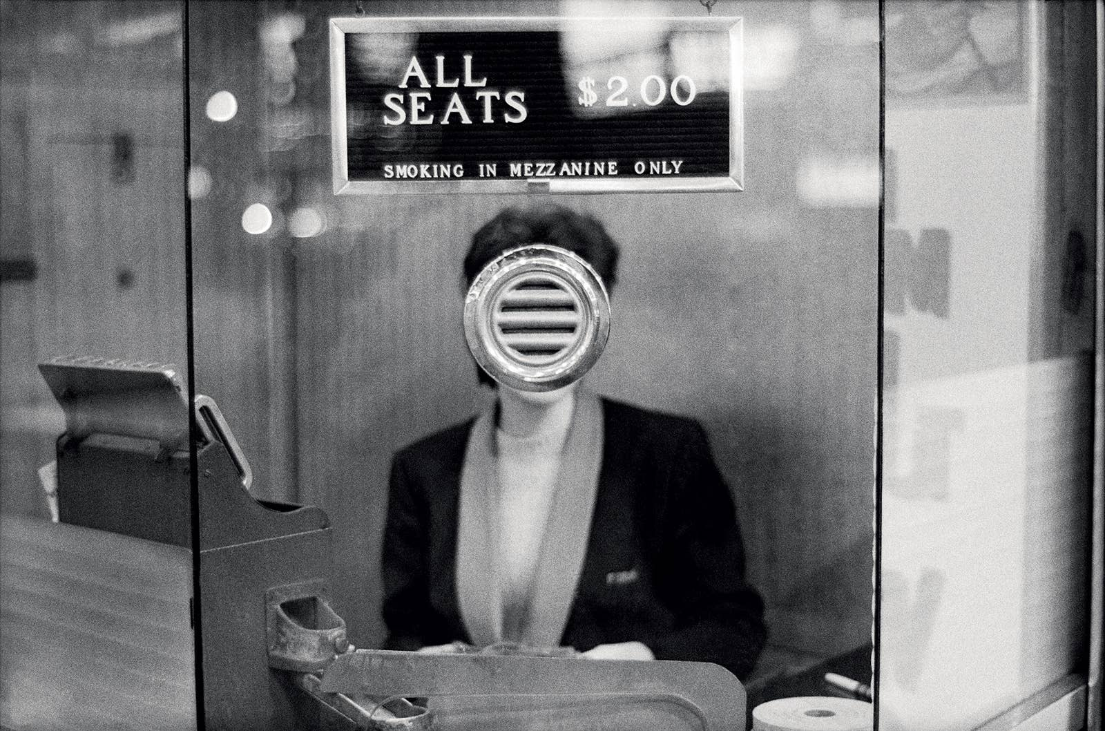 A woman's face is obscured as she sits in the ticket booth at a movie theater